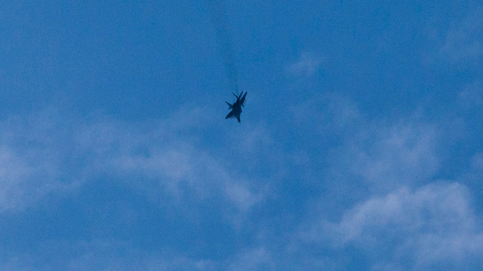 A Ukrainian military jet flies over a shot down Ukrainian Army helicopter outside Slovyansk, Ukraine, Thursday, May 29, 2014. (AP / Alexander Zemlianichenko)