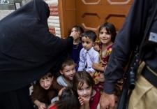 Pakistani children wait to receive polio vaccine