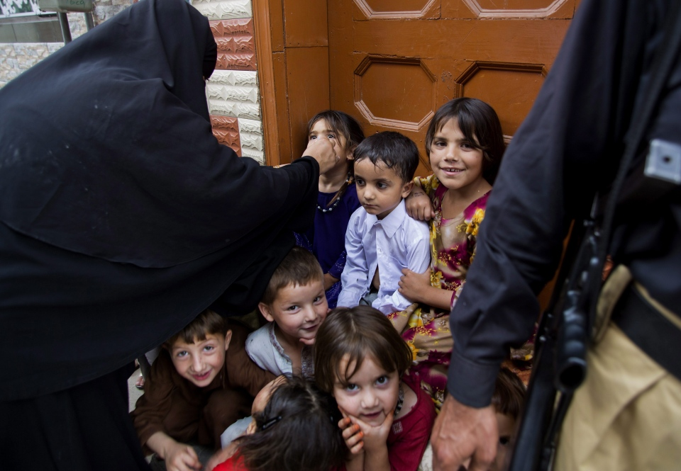Pakistani children wait their turns to receive polio vaccines in Rawalpindi, Pakistan, Tuesday, May 6, 2014. Pakistan's health minister says the country is taking extra ordinary measures to meet the new situation it is going to face after polio travel restrictions. (AP Photo/B.K. Bangash)