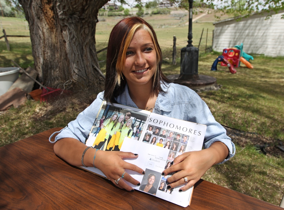 Wasatch High School sophomore Shelby Baum, 16, points to yearbook proof, left, and her altered school yearbook photo, right, Thursday, May 29, 2014, in Heber City, in Utah. (AP Photo/Rick Bowmer)