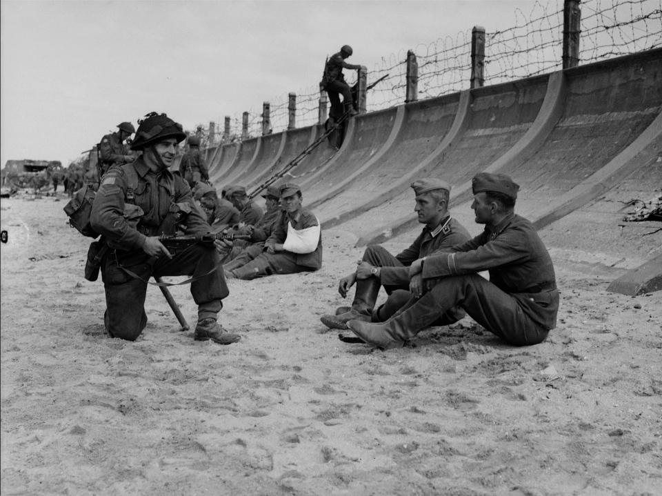 A group of German prisoners, captured by Canadian troops sit on Juno Beach in Normandy, France on June 6, 1944. (Frank L. Dubervill / National Archives of Canada)