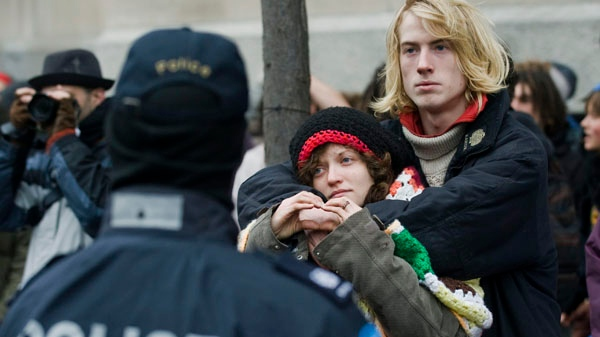Two demonstrators hold each other next to the Occupy Montreal site on Friday, November 25, 2011, after police moved in and closed down the camp. THE CANADIAN PRESS/Graham Hughes