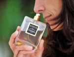 A woman takes a sniff of a perfume from Chanel in Gelsenkirchen, Germany, Thursday, July 10, 2008. (AP Photo/Martin Meissner)