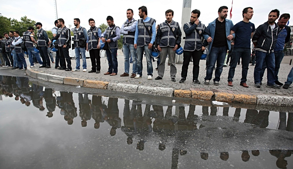 Turkish security members watch as they close the city's landmark Taksim Square and Gezi Park on the first anniversary of last year's protests in Istanbul on Saturday, May 31, 2014. (AP / Emrah Gurel)