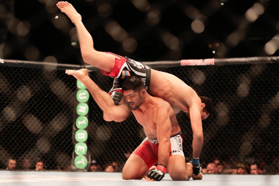 Mark Munoz, bottom, from the United States fights Iranian born Gegard Mousasi in a middleweight fight during the UFC Fight Night mixed martial arts event in Berlin, Saturday, May 31, 2014. Gegard Mousasi won the fight. (AP Photo/Markus Schreiber)
