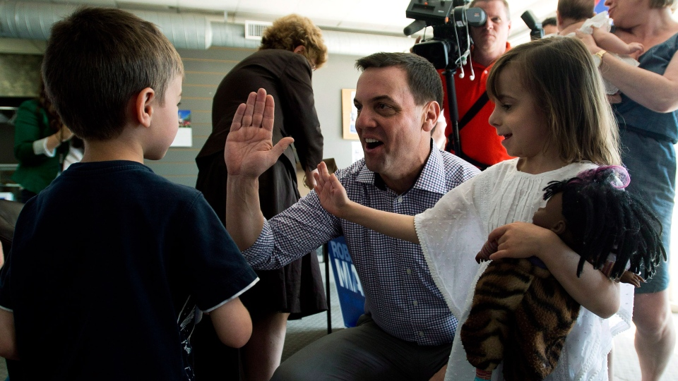Ontario Conservative Leader Tim Hudak, centre, and his daughter Miller Hudak, right, (6) high five Samuel Wexler, left, (6) during a campaign stop in Toronto on Sunday, June 1, 2014. (Nathan Denette / THE CANADIAN PRESS)