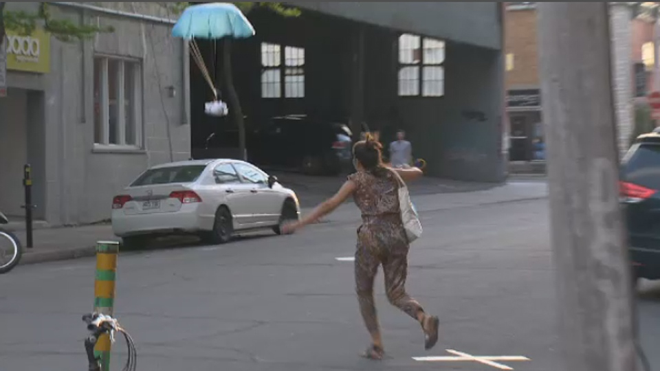 A woman chases after a grilled cheese sandwich falling to Earth in a parachute in Montreal on June 1, 2014