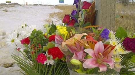 Flowers are seen at the scene of a tragic accident that took the lives of three young men near Beaumont on Saturday, Nov. 26, 2011.