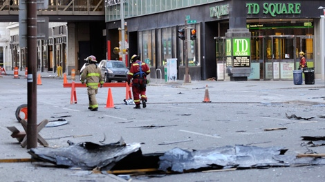 Fiefighters inspect damage after windows blew out and parts of an office tower were taken off by high winds in Calgary, Alberta on Sunday, Nov. 27, 2011. (Larry MacDougal / THE CANADIAN PRESS)