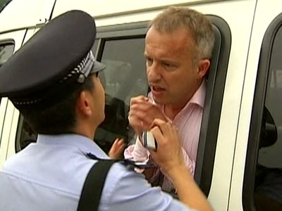 John Ray of London-based ITV News asks a Chinese police officer whether he has been arrested, after being detained while covering a protest in Beijing on Wednesday, Aug 14, 2008.
