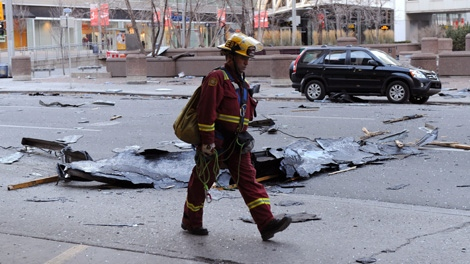 A firefighter walks past broken window glass and parts of an office tower blown off by high winds in Calgary, Alberta on Sunday, Nov. 27, 2011. (Larry MacDougal / THE CANADIAN PRESS)
