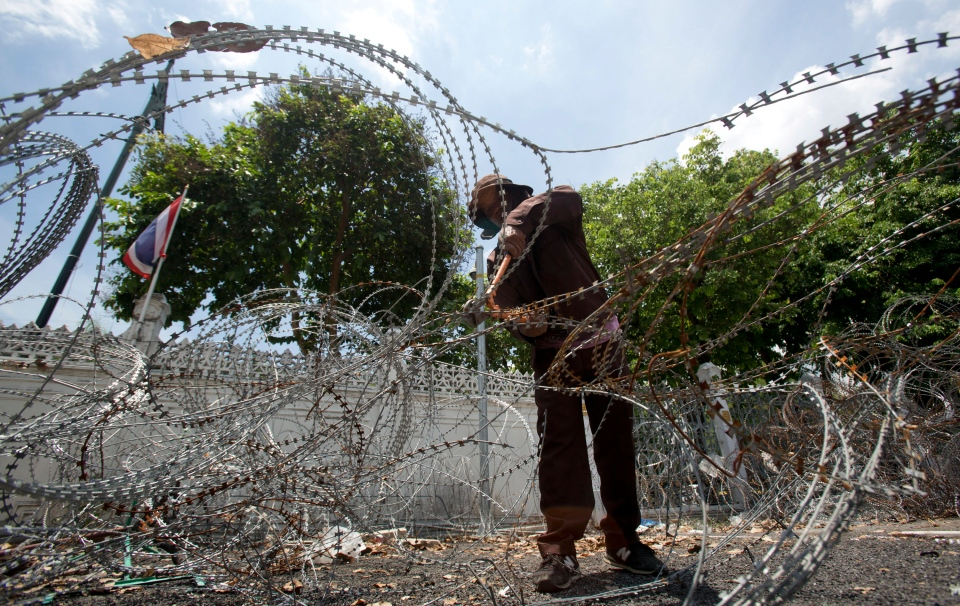 A Thai worker removes barbed wire from the government house in Bangkok, Thailand Tuesday, June 3, 2014. (AP / Sakchai Lalit)
