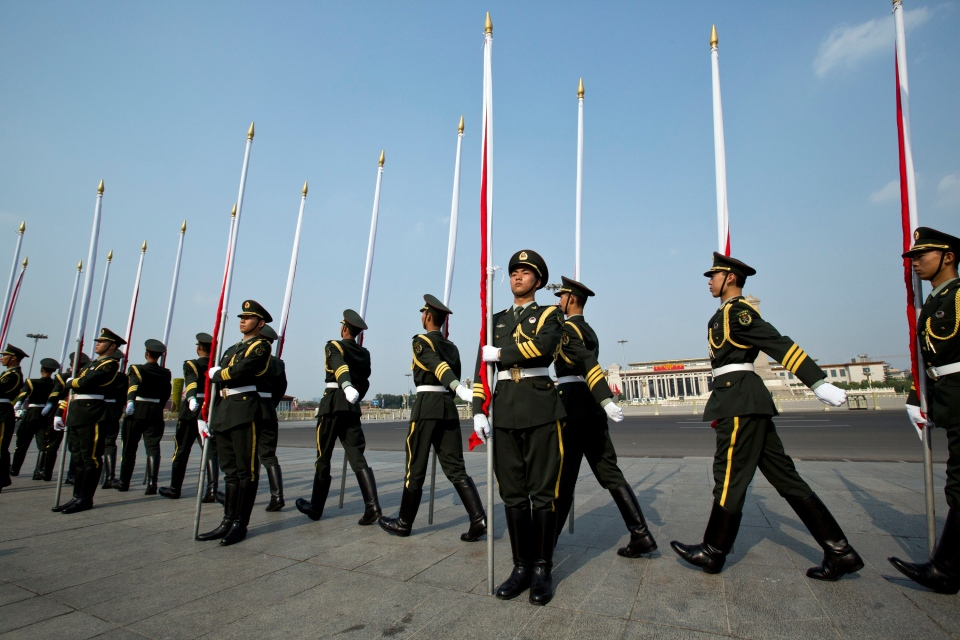 People's Liberation Army soldiers holding red flags march to their positions before an honor guard performance for a welcome ceremony outside the Great Hall of the People near Tiananmen Square, back, which is closed to the public in Beijing, Tuesday, June 3, 2014. (AP / Alexander F. Yuan)