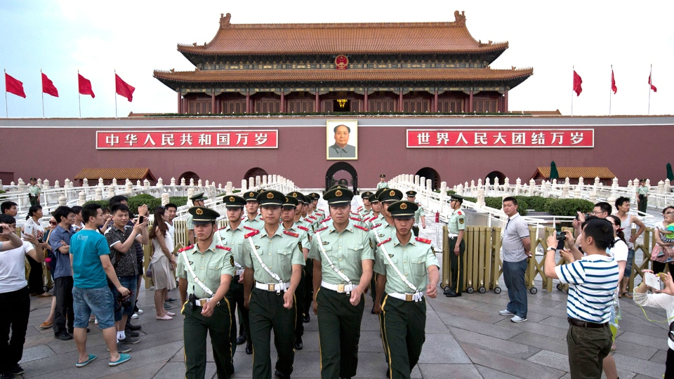 Paramilitary policemen march out of Tiananmen Gate to clear tourists from the area for a flag-lowering ceremony on Tiananmen Square in Beijing, May 28, 2014. (AP / Alexander F. Yuan)