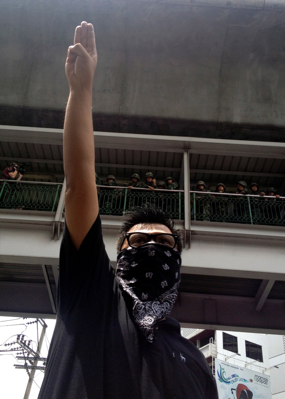 An anti-coup protester gives a three-finger salute as soldiers keep eyes on him from an elevated walkway near a rally site in central Bangkok, Thailand, Sunday, June 1, 2014. (AP / Thanyarat Doksone)