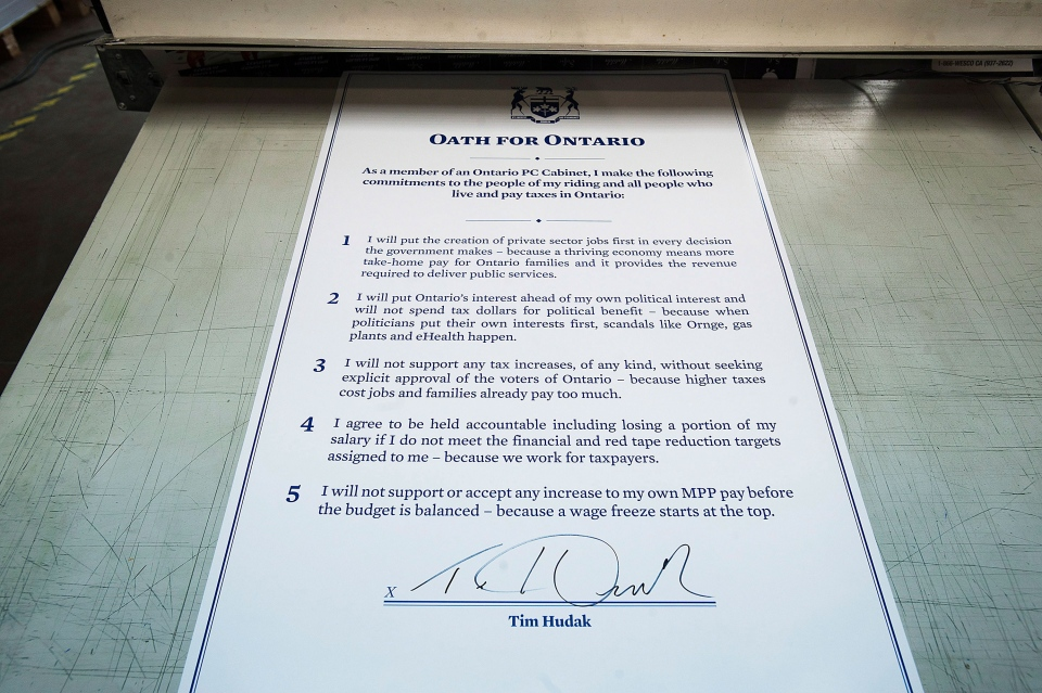 An oath signed by Ontario Conservative Party Leader Tim Hudak to the people of Ontario is displayed during a campaign event at MI5 Print and Digital Communications Inc. in Markham, Toronto on Tuesday June 3, 2014. (Aaron Vincent Elkaim / THE CANADIAN PRESS)