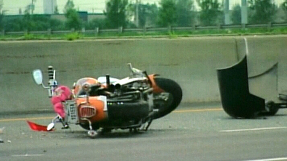A wrecked motorcycle lays behind a car that had parked in the left-hand lane of Highway 30, in Candiac, Que., June 27, 2010.