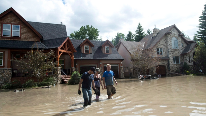 People walk away from flooded homes in Calgary, Alta., on Monday, June 24, 2013. (The Canadian Press/Nathan Denette)