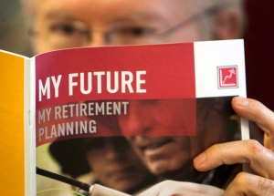 A man looks over a brochure offering various retirement savings options, in Montreal on Friday, February 3, 2012. (Ryan Remiorz / THE CANADIAN PRESS)