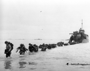 U.S. reinforcements wade through the surf from a landing craft in the days following D-Day and the Allied invasion of Nazi-occupied France at Normandy during World War II in June 1944. (AP / Bert Brandt)