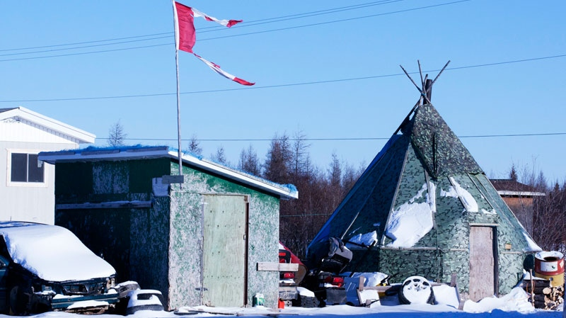 The remains of a Canadian flag can be seen flying over a building in Attawapiskat, Ont. Tuesday, Nov. 29, 2011. (Adrian Wyld / THE CANADIAN PRESS)