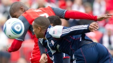 Toronto FC's Andy Iro (left) beats New England Revolutions' Darrius Barnes (centre) and Demitrius Omphroy to send a header narrowly wide of the goal during second half MLS action in Toronto on Saturday October 22, 2011. (Chris Young / THE CANADIAN PRESS)