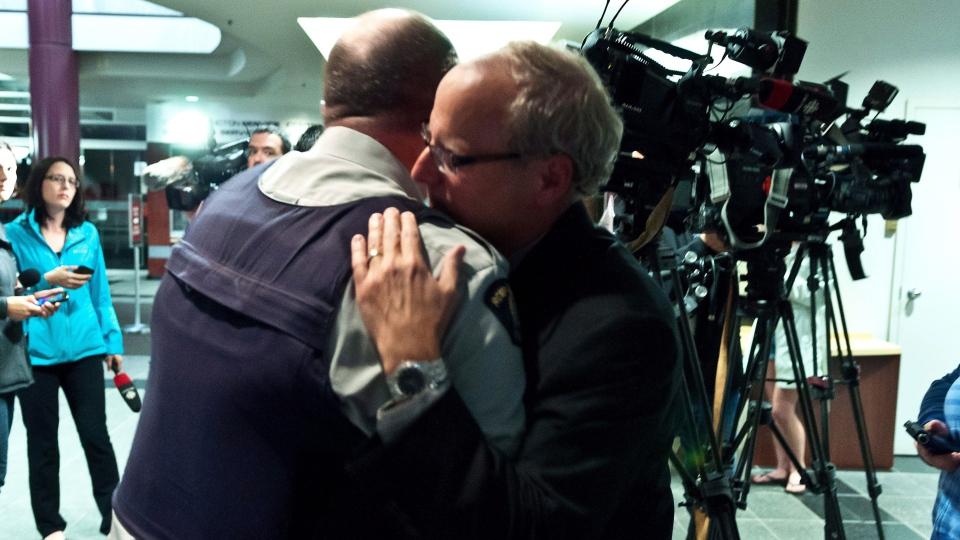 RCMP officer Damien Theriault, left, and Mayor George LeBlanc hug after addressing the media during a late press conference at City Hall in Moncton, N.B.on Wednesday June 4, 201. (Marc Grandmaison / THE CANADIAN PRESS)
