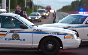 RCMP officers use their vehicle to create a barrier during the search for a man suspected of fatally shooting three officers in Moncton, N.B., on Wednesday, June 4, 2014. (The Canadian Press/Marc Grandmaison)