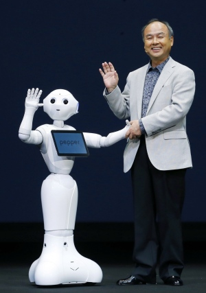 Softbank Corp. President Masayoshi Son, right, and Pepper, a newly developed robot, wave together during a press event in Urayasu, near Tokyo, Thursday, June 5, 2014. (AP / Kyodo News)