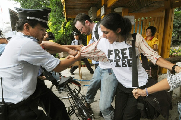 Pro-Tibet activists are detained by Chinese police after staging a protest near the main Olympics venue in Beijing on Wednesday, Aug. 13, 2008. (AP / Kyodo News)