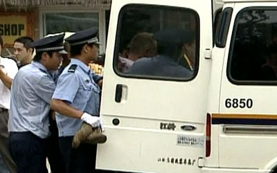 British journalist John Ray struggles with Chinese police as they force him into a vehicle in Beijing on Wednesday, Aug 14, 2008.