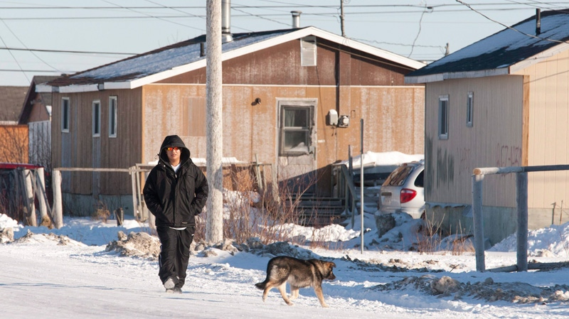 A man walks down the street in Attawapiskat, Ont., Tuesday Nov. 29, 2011. (Adrian Wyld / THE CANADIAN PRESS)