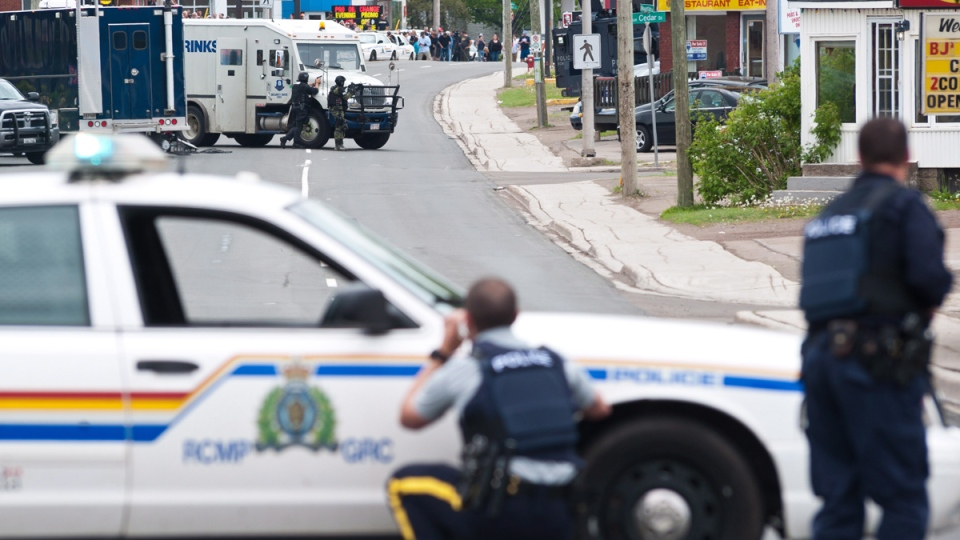 Police keep watch on a house as the search for a heavily armed gunman suspected to have shot three Mounties dead and injured two others continues in Moncton, N.B., Thursday, June 5, 2014. (Marc Grandmaison / THE CANADIAN PRESS)