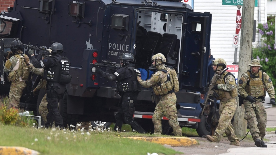Heavily armed RCMP officers enter a residence during the manhunt for the shooting suspect in Moncton on Thursday, June 5, 2014. (Andrew Vaughan / THE CANADIAN PRESS)