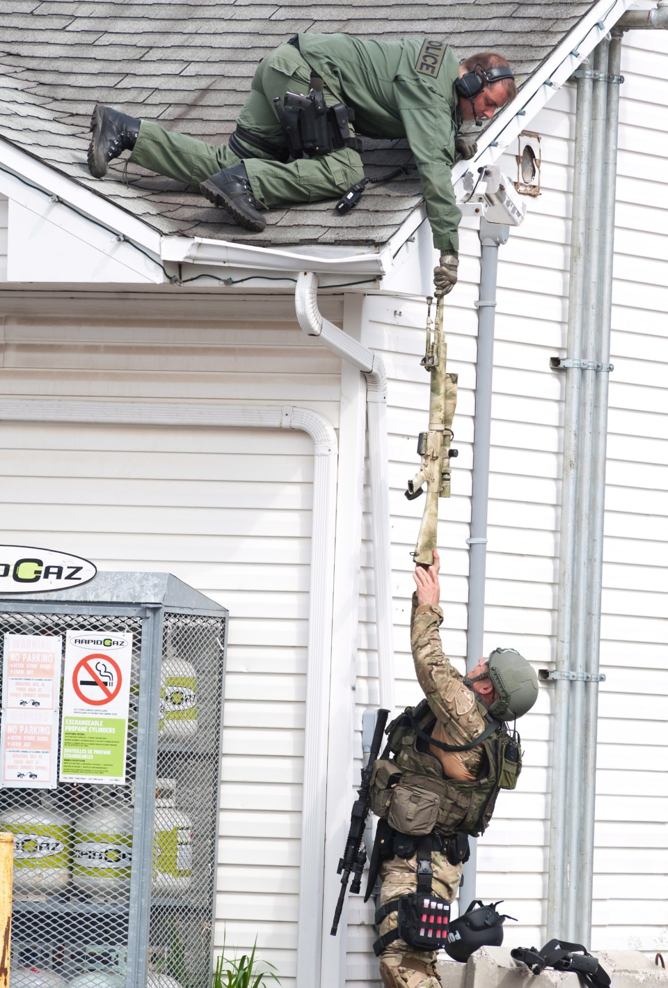 A weapon is passed to an RCMP Emergency Response Team member on the roof of a house in Moncton, N.B., Thursday, June 5, 2014. (Marc Grandmaison / THE CANADIAN PRESS)