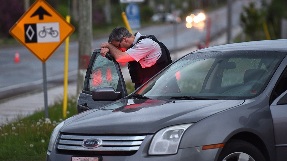 An RCMP officer rests his head at a roadblock in Moncton, N.B. on Thursday, June 5, 2014. (Andrew Vaughan / THE CANADIAN PRESS)