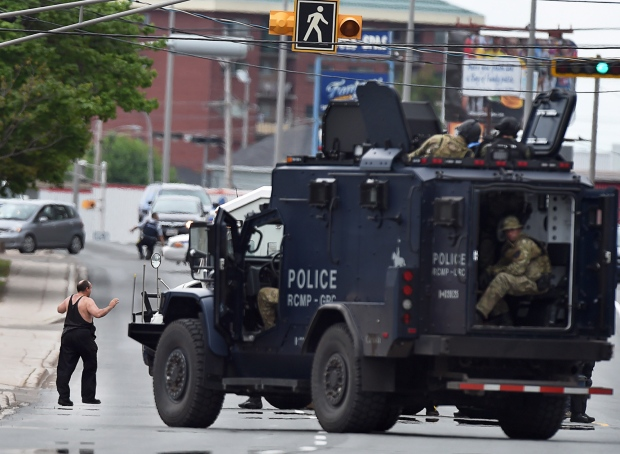 A nerve-wracking manhunt came to an end early Friday morning after police apprehended the suspect wanted in one of the worst mass shootings in the RCMP's history that left three Mounties dead and two others wounded in Moncton.<br><br>A resident of a boarding house is evacuated by emergency response officers as they search a building in Moncton, N.B. on Thursday, June 5, 2014. (Andrew Vaughan / THE CANADIAN PRESS)