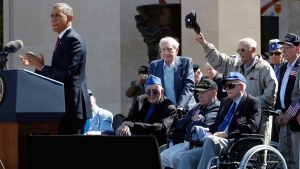 U.S. President Barack Obama, left, acknowledges veterans as he speaks at the Normandy American Cemetery, at Omaha Beach as he participates in the 70th anniversary of D-Day in Colleville sur Mer in Normandy, France, Friday, June 6, 2014. (AP Photo/Charles Dharapak)