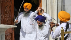 Members of a hardline Sikh group clash with guards of the Sikh's holiest shrine, the Golden Temple, in Amritsar, India, Friday, June 6, 2014. (AP / Sanjeev Syal)
