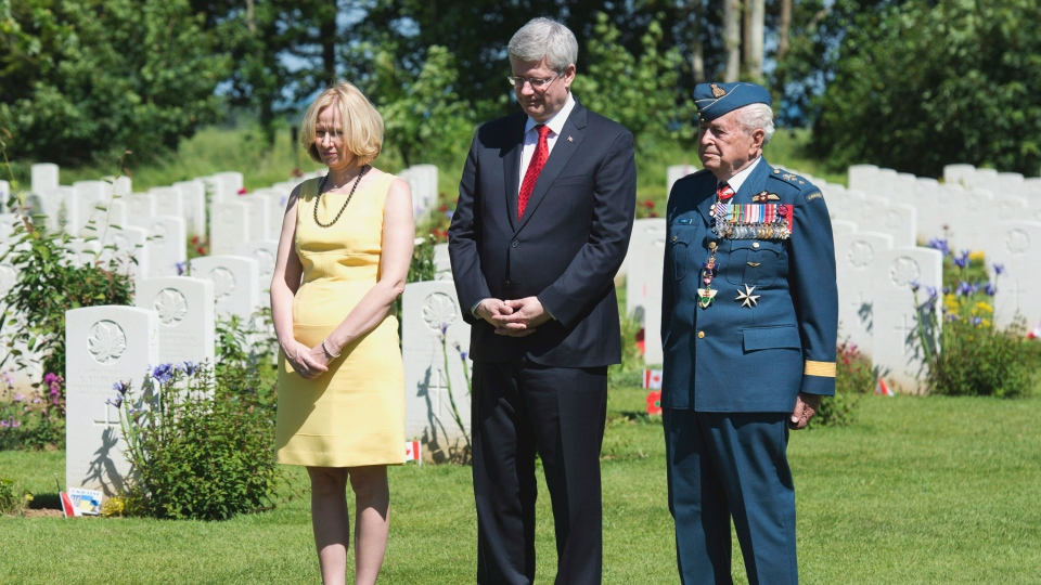 Prime Minister Stephen Harper speaks with Major-General Richard Rohmer as he walks through the Canadian military cemetery Friday June 6, 2014 in Beny-sur-Mer, France. (Adrian Wyld / THE CANADIAN PRESS)