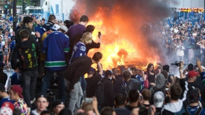 Stanley Cup rioters are seen next to a burning car in Vancouver on June 15, 2011. (Geoff Howe / THE CANADIAN PRESS)