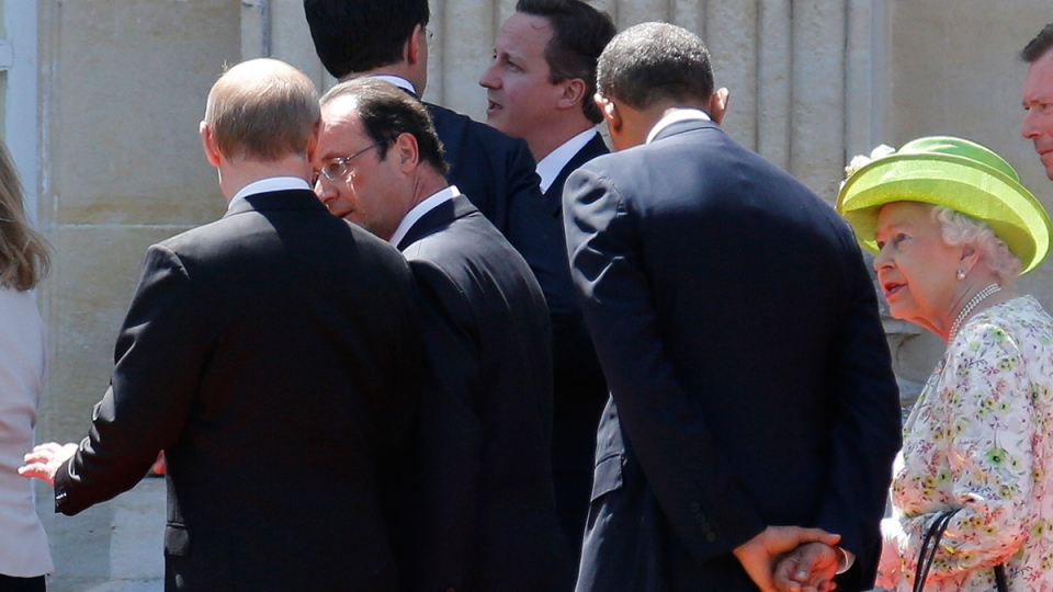 Russian President Vladimir Putin, left, talks to French President Francois Hollande, 2nd right, as they walk next to U.S. President Barack Obama, centre, Queen Elizabeth, Luxembourg's Grand Duke Henri and Britain's Prime Minister David Cameron after posing for a group photo for the 70th anniversary of the D-Day landings at at Benouville castle, in Normandy, France, Friday, June 6, 2014. (Regis Duvignau, pool)