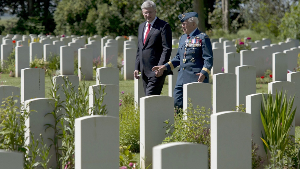 Prime Minister Stephen Harper speaks with Major-General Richard Rohmer as he walks through the Canadian military cemetery, in Beny-sur-Mer, France, Friday, June 6, 2014. (Adrian Wyld / THE CANADIAN PRESS)