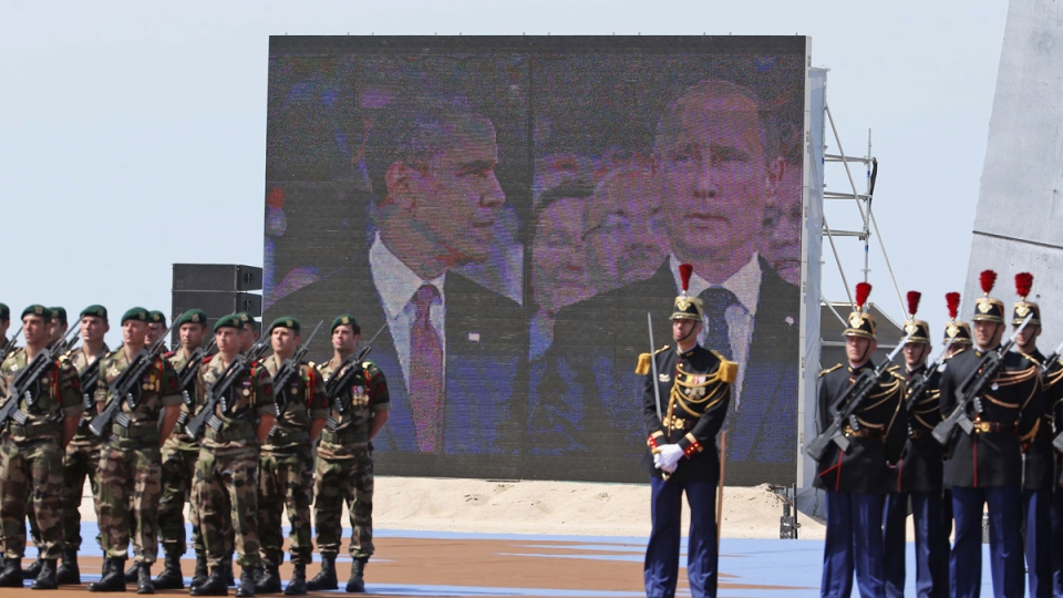 U.S. President Barack Obama and Russian President Vladimir Putin are shown on a split screen as they take their seats at celebrations for the 70th anniversary of D-Day at Sword Beach in Ouistreham, France, Friday, June 6, 2014. (AP / Charles Dharapak)