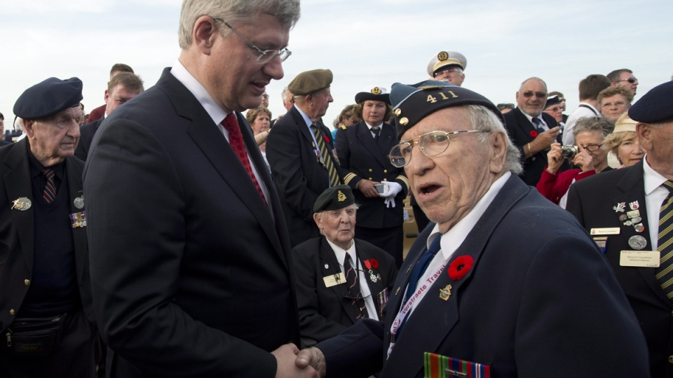 Prime Minister Stephen Harper shakes hands with a Canadian veteran following the Ceremony of Rememberance at Juno Beach in Courcelles-sur-mer, France, Friday, June 6, 2014. (Adrian Wyld / THE CANADIAN PRESS)