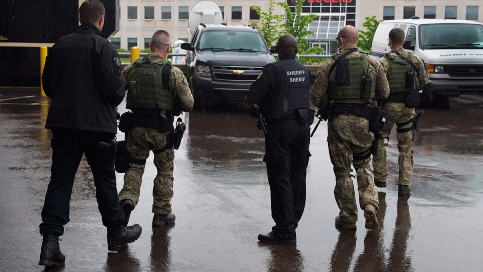 Police officers head from the court appearance of Justin Bourque, the suspect in one of the worst mass shootings in the RCMP's history, in Moncton, N.B. on Friday, June 6, 2014. (Andrew Vaughan / THE CANADIAN PRESS)