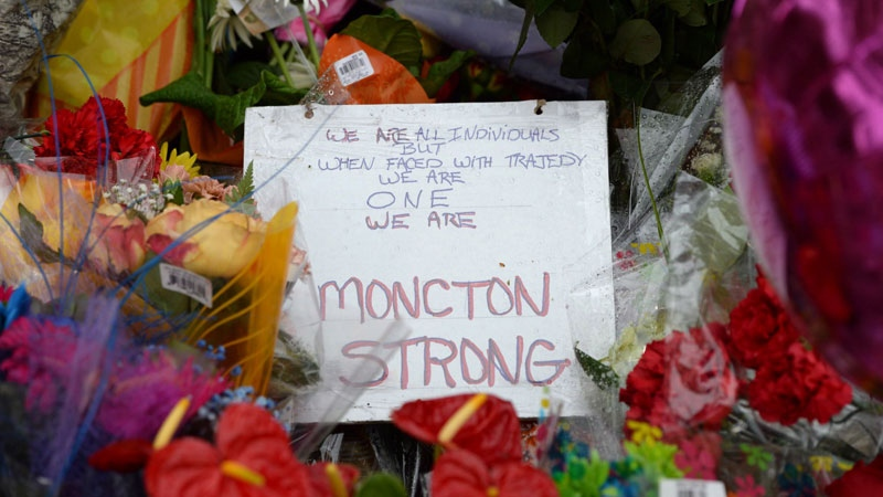 A handwritten sign and flowers are seen at RCMP headquarters in Moncton, N.B., on Friday, June 6, 2014. RCMP say a man suspected in the shooting deaths of three Mounties and the wounding of two others in Moncton was unarmed at the time of his arrest early Friday and was taken into custody without incident. THE CANADIAN PRESS/Sean Kilpatrick