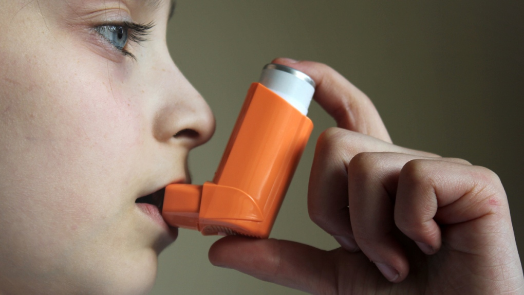 A child uses an inhaler to treat asthma