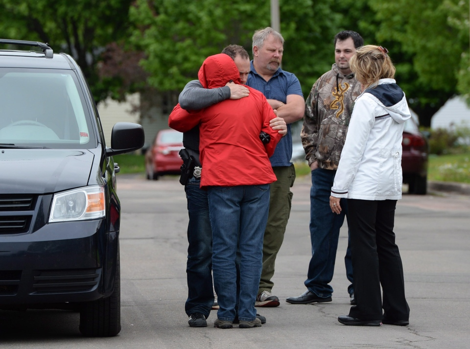 A resident is hugged by an officer at the corner of Mailhot Avenue and Isington Street in Moncton, N.B. on Saturday, June 7, 2014 where one of three RCMP officers was shot to death. THE CANADIAN PRESS/Sean Kilpatrick