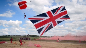 A paratrooper drags a large Union flag as he lands during a D-Day commemoration in Ranville, western France, Thursday, June 5, 2014, on the eve of the 70th anniversary of the World War II Allied landings in Normandy. (AP Photo/Thomas Bregardis, pool)